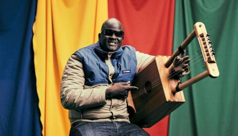 photograph of blind South Sudanese musician Gordon Koang sitting on a stool holding a traditional Nuer stringed instrument.